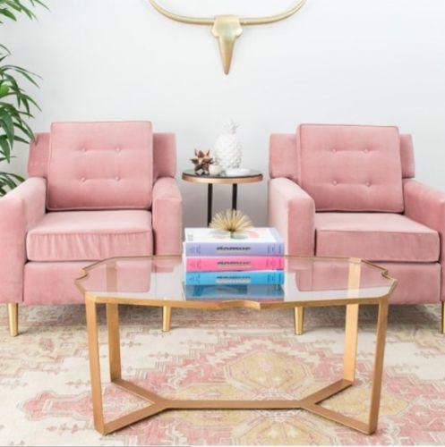 Dos sillones rosas tapizados en terciopelo, una cabeza de vaca, mesa de centro dorada y tonos pastel son el mix perfecto para estar en tendencia.