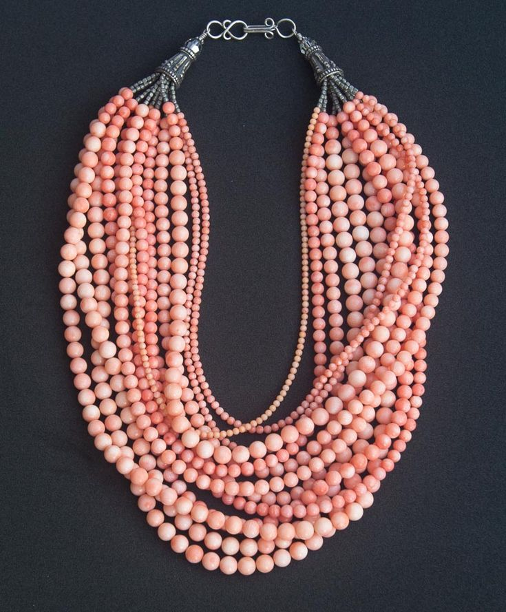 Ma-zu - Chinese Goddess of sea. This beautiful one of a kind necklace features 13 strands of natural angel skin coral mixed with dyed sea bamboo coral in different shades of salmon and pink. Several different sizes of round coral beads and the subtle variations in color enhance the appeal of this gorgeous necklace. Tiny tribal silver beads from India lead to sterling silver cones and clasp.