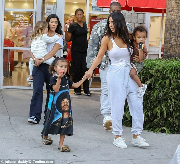 Time for some fun: The entrepreneur carried her son Saint while holding North's hand
