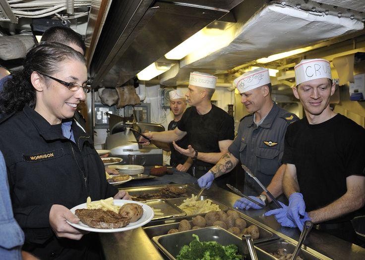 Ordinary Seaman (OS) Phyllis Morrison (left), member of Her Majesty's Canadian Ship (HMCS) Athabaskan, stands in the line up of the main galley during Task Group Exercise (TGEX) out in the Atlantic Ocean, on 18 November 2010. Served by (from left to right) OS Nigel Appler, Leading Seaman Scott Delaney, Corporal Shane Croney and OS Colin Pynn, they helped the cooks to prepare and served dinner. Photo Corporal Johanie Maheu