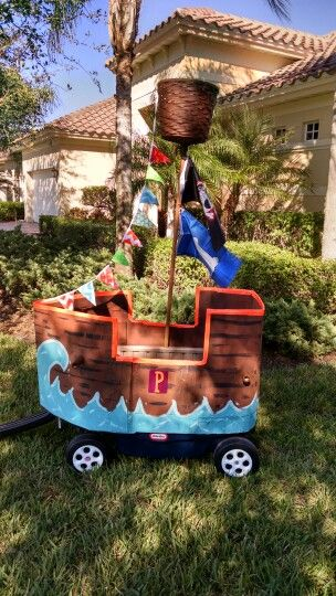 Pirate ship wagon. I made this pirate ship out of cardboard using duct tape, a mixture of spray paint & acrylic paint. The flag pendant was made out of scrap quilting fabric. The crows nest was made out of an old wicker basket & mop handle.