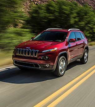 A red 2017 Jeep Cherokee Canada being driven on the road