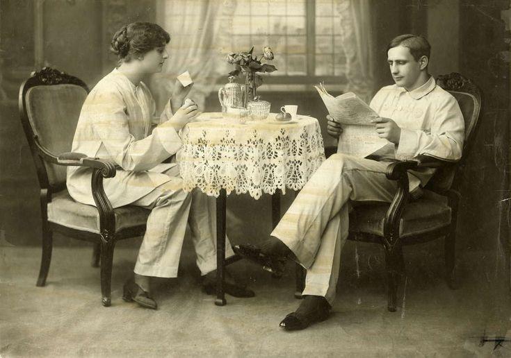 Badmode 1913. Thee drinkend en kranten lezend stel aan een tafeltje in badkleding / strandkleding (jasje en pantalon / broek) zoals die gedragen werd in Engelse badplaatsen. 1913, plaats onbekend.
