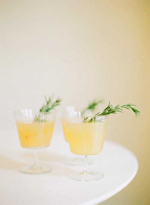 A pear-ginger fizz signature cocktail made with pear juice with vodka and ginger ale. Garnish each glass with fresh rosemary | Brides.com