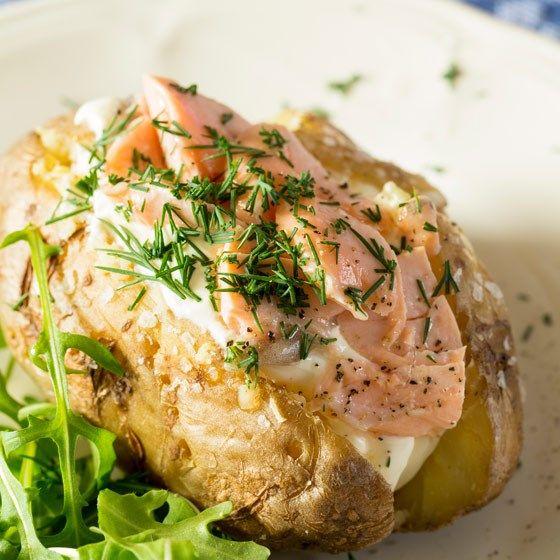 Gepofte aardappel met zalm, zure room en dille 4 grote, kruimige aardappels, bijv. Eigenheimer 25 ml zure room 150 gr zalm 2 el verse dille scheutje citroen- of limoensap wat peper en zout