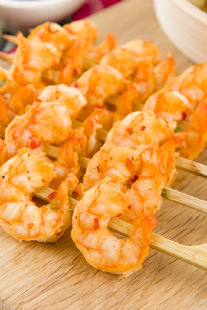 Bereiden:Marineer de scampi's: Steek op elke brochette 4 scampi's en kruid af met peper en zout. Meng voor de marinade de rest van de ingrediënten, lepel deze over de brochettes en laat 30 minuten marineren in de koelkast. Maak de pastasalade: Kook de pasta al dente in licht gezouten water en laat afkoelen. Meng de pasta met de rest van de ingrediënten en breng op smaak met peper en zout. Werk af: Gril de scampi's kort op de bbq en serveer samen met de pastasalade.