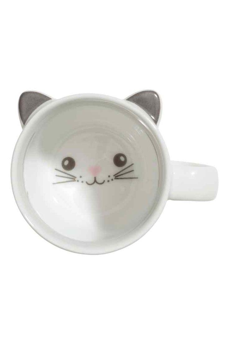Taza de porcelana: Taza de porcelana con orejas y motivo impreso en el fondo. Diámetro 7,5 cm. Alto 7,5 cm.