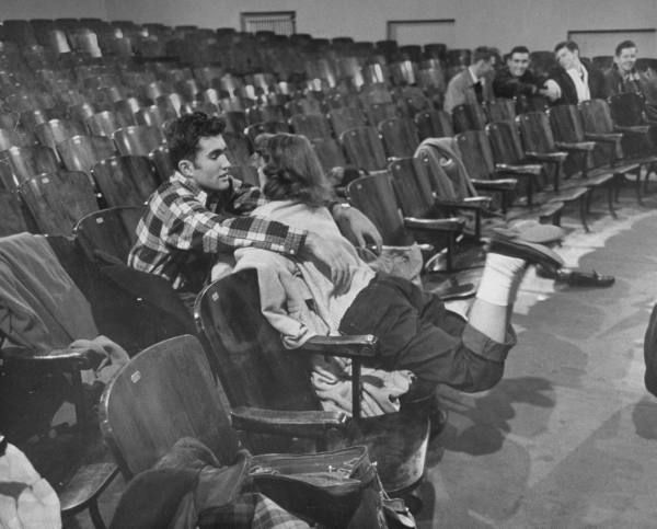 A teenage couple in the auditorium of their high school. Photograph by Yale Joel. Winchester, Massachusetts, February 1950.