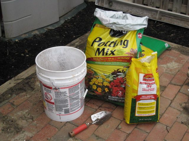 How to Get New Grass to Grow in the Heat of Summer: Seed With Potting Soil      Grass seeding supplies--- a bag of seed and another larger one of potting soil and used a 5-gallon paint bucket and a trowel to mix the two together. (Potting soil has two benefits over topsoil, which is most commonly used: it contains fertilizer and it tends to retain moisture a little better after watering. Both help the new roots' growth.)