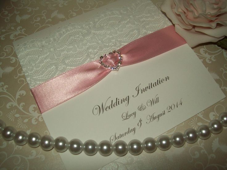 A pretty ribbon and lace embellished wedding invitation with a sparkly diamante heart, the ribbon can be changed to any colour
