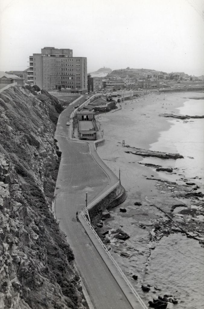Marine Drive along Newcastle Beach. Newcastle Hospital is the large building, Nobbys is in the distance and Fort Scratchley is to the right. Vinco Series No. 52.   This image was scanned from a photograph in the Newcastle and Hunter District Historical Society archives which are held by Cultural Collections at the University of Newcastle, Australia.  If you have any information about this photograph, please contact us.  Please contact us if you are the subject of the image, or know the…