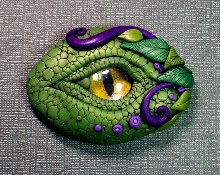 "This was a custom order. They asked me to re-create my woodland dragon eye but add touches of purple. I am getting better at etching all of the scales by hand. Takes a while! I painted the eye myself this time and it turned out pretty well. I want to get better metallic paints for this next time. :) It is 2.5"" long and can be made into a pendant, used as a little paperweight or you can put a magnet on the back and stick him on the fridge. ^^"