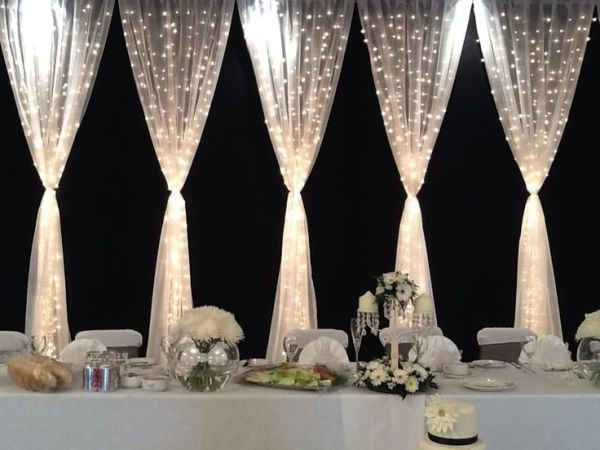 Pretty backdrop for the wedding party table. Gorgeous gorgeous gorgeous.  Tulle and twinkle lights make beautiful wedding decor. by monique