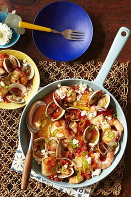 Shellfish and Tomato Stew • ¾ cup white wine  1¼ pounds clams • 2 tablespoons olive oil, plus extra to finish • 2 cloves garlic, peeled and thinly sliced • 1 teaspoon tomato paste • 1 pound ripe tomatoes, cut into ½-inch dice • ½ teaspoon sugar • 1 tablespoon fresh oregano, roughly chopped • ½ teaspoon salt, plus extra to taste • Freshly ground pepper, to taste • 1 lemon • 6 ounces large scallops • 7 ounces large shrimp, peeled   and deveined • 2 ounces feta, crumbled • 1 scallion, outer…