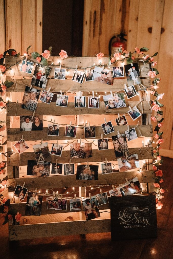 DIY photo board for your wedding reception!  Simply get a wooden slat board and hang photos off clotheslines with clothespins.  Love the additional Christmas lights as well to really light it up! Photo taken at THE SPRINGS Event Venue.  Follow this pin to our website for more information, or to book your free tour! SPRINGS location:  Edmond, OK Photographer:  Kelcy Leigh Photography #diywedding #diyweddingdecor #diyweddingreception #diyreception #diybride #weddingdecor #weddingideas