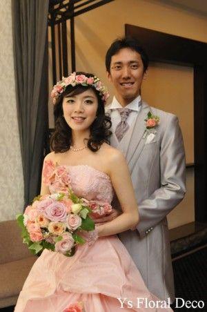 こちらの新婦さんのお色直しです。お花飾りのついた大人かわいいピンクのドレス、ウェーブのあるダウンのヘアスタイルと花冠。フォーマルな白ドレスからがらりと印象...