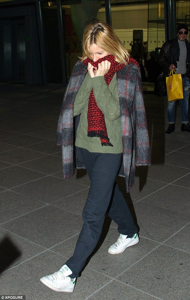 Hiding: Sienna Miller, 33, appeared uncharacteristically shy as she went make-up free in a relaxed ensemble while arriving at London's Heathrow Airport on Monday