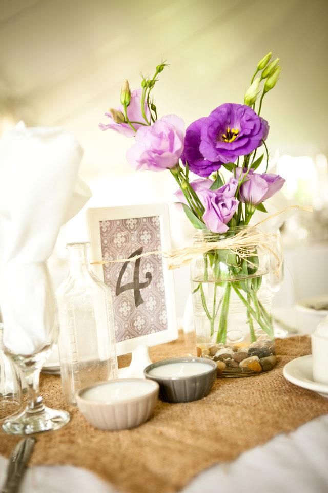 Rustic wedding décor including antique mason jars and burlap table runners.