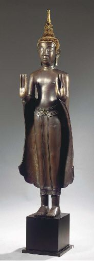 a laos bronze figure of buddha sakyamuni 17th/18th century Standing in samabhanga, both hands in abhayamudra, wearing samghati, his face with serene expression, mother-of-pearl inlaid eyes, aquiline nose, smiling lips, elongated earlobes and curled hairdress and usnisha surmounted by a flame, traces of gilding and black lacquer 149.5 cm high, mounted