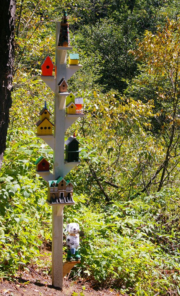 My brother did this up at his cabin. He got small birdhouses from the dollar store and painted them bright colours and made the post to sit them on.