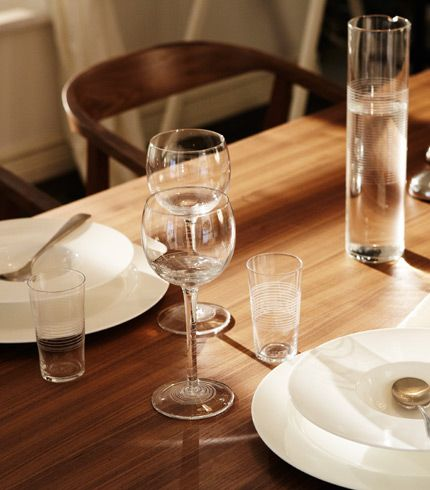 STOCKHOLM dining table in walnut set with STOCKHOLM red wine glasses, carafe and STOCKHOLM white plates, by IKEA.