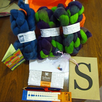 """Sues153 from kreachr - """"What a wonderful surprise. Fab fibre from Kate's Heavenly Wools that I have been wanting to try out in great colours. A special S book to plot and scheme in with pencils to do that with. A knitting gauge and ruler that I can take on the go. Plus stitch markers in a beautiful organdy bag (the sort I love too - how did you know) My fav Cardomom choc from Schoc - mmmmm and as if that wasn't enough a colour in Gift card from Amazon."""""""