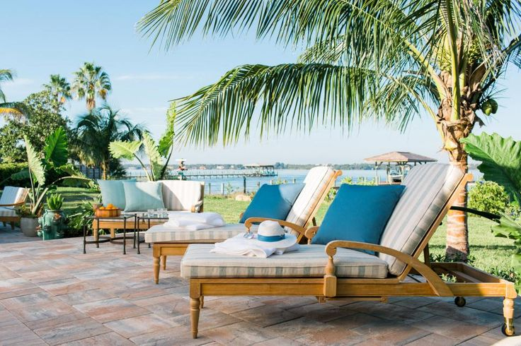 A raised sun deck area is furnished with teak wood lounge chairs, a cushioned bench and accent tables. It affords a view of the river and the pool.