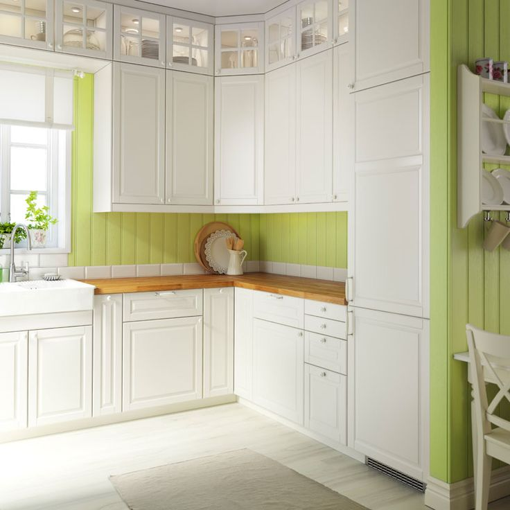Traditionelt køkken med hvide skabe, bordplader af træ, vitrinelåger og integrerede hvidevarer