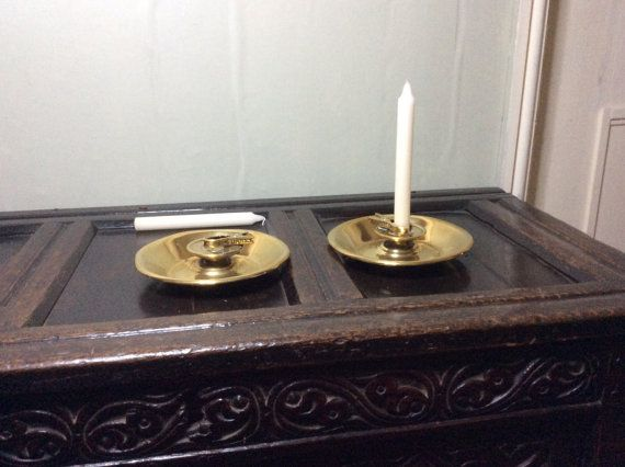 This pair of candle holders have saucer-shaped bases they have no candle socket attached but flat drip pans on short standards, on which clamps resembling crabs pincers are attached. When pressed they work on a spring action principle to hold and burn candles and candle ends of various