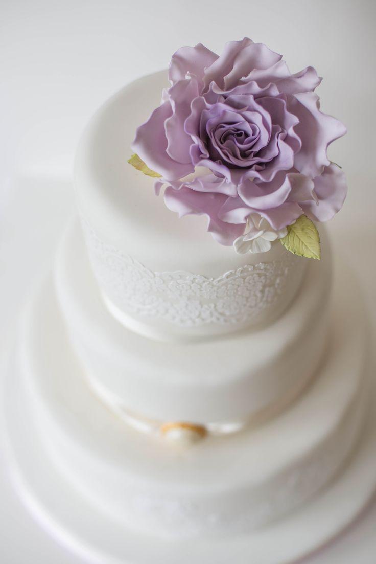 Klassische und romantische Hochzeitstorte mit Spitze und Vintagerose in flieder