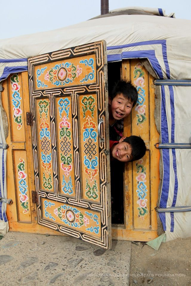 Mongolian boys laughing as they peek out from their yurt (ger).