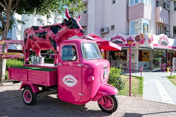Ярко-розовая машина около кафе мороженого