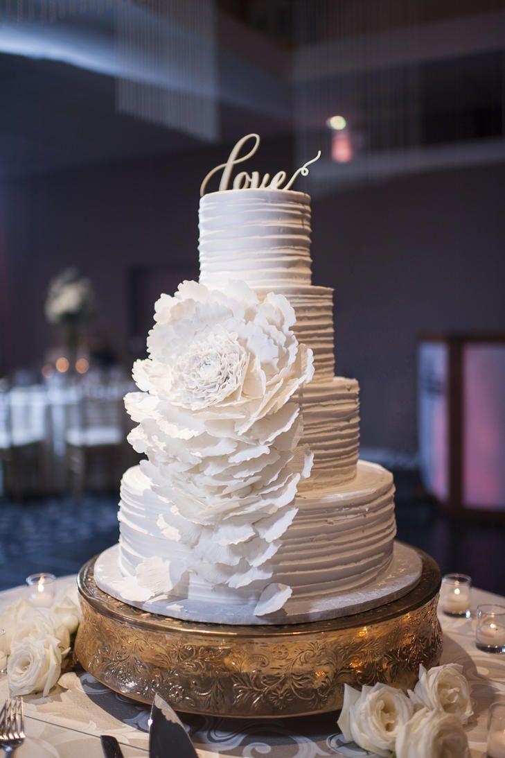 Four-tier textured buttercream and fondant flower cake