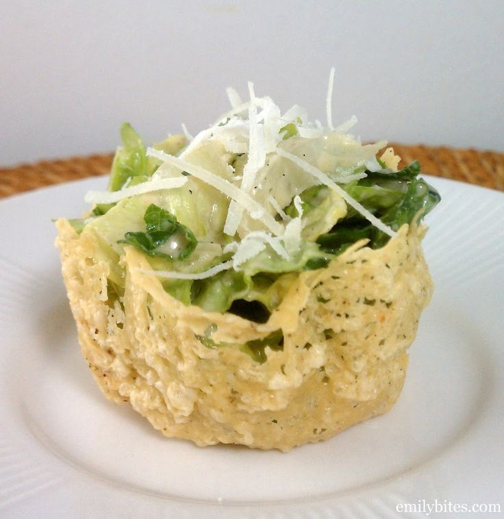 A white plate with a Caesar Salad Parmesan Cup stuffed with delicious creamy Caesar Salad.