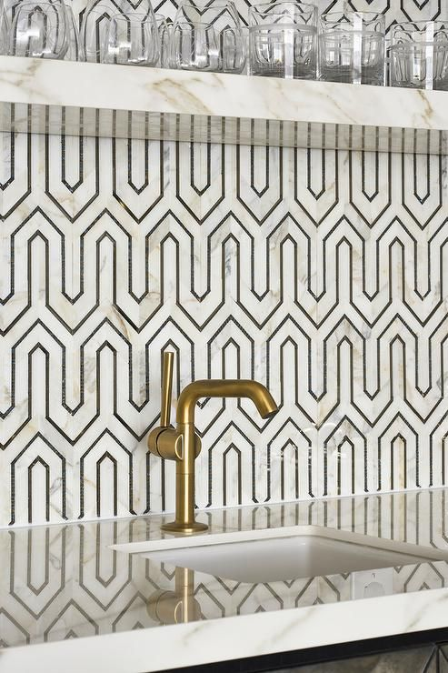 Clad in black and white geometric backsplash tiles, this gorgeous contemporary wet bar is fitted with a floating marble shelf fixed above a marble countertop finished with a curved square sink with a brushed gold faucet kit.