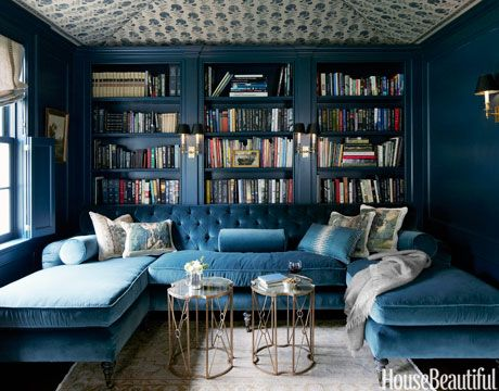 The tufted U-shaped sofa is upholstered in a blue Schumacher silk velvet very close to the color of the walls.