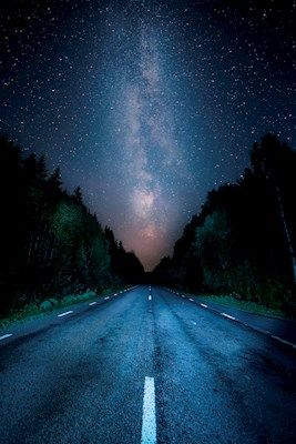 Amazing colorful photograph of the Milkyway above a road in the middle of the forest. Photo by Christian Andersson, available as poster at printler.com, the marketplace for photo art.