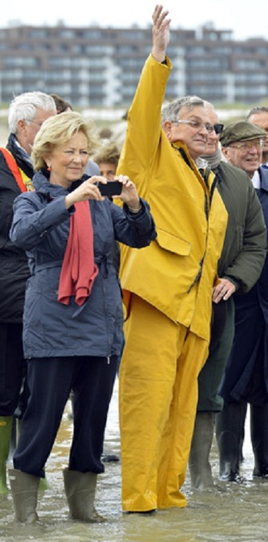 Queen Paola of Belgium (L) takes a picture during a royal visit to the 'Orde van de Paardevisser', shrimp-fishermen on horses, 13 June 2013 in Oostduinkerke, Koksijde