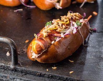 Hotdog Louisiana style Ingrediënten      1 verse hotdog van goede kwaliteit varkensvlees     25 g cheddar     2 plakken bacon     1 tl barbecuekruiden     1 brioche hotdogbroodje     1/2 verse jalapeño     2 el coleslaw     1 el mosterd     1 el barbecuesaus     1 el gebakken uitjes