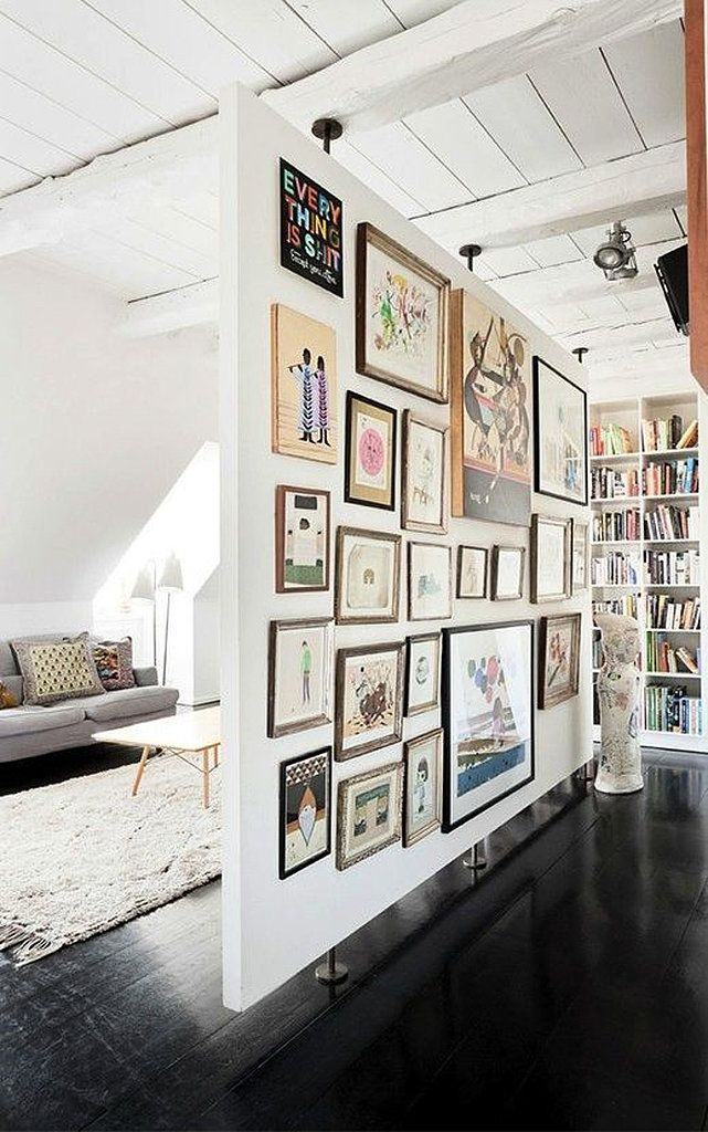 This space turned a room divider into art with a gallery wall. By filling the entire wall, the floating wall becomes both the backdrop and the focal point for the living room.  Photo by The Apartment  via Style Me Pretty