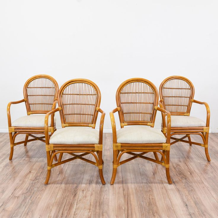 This set of 4 tropical dining chairs are featured in a bent rattan with a glossy teak finish. These chairs are in great condition with curved arms, a woven back and white upholstered seat cushion. Beach chic chairs perfect for an outdoor dining set! #tropical #chairs #chair #sandiegovintage #vintagefurniture