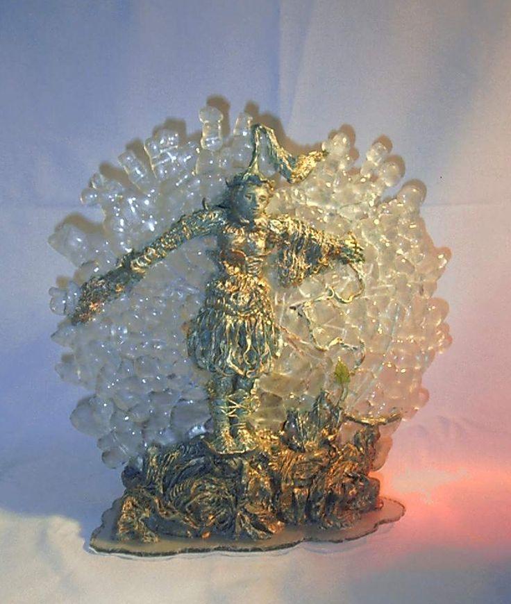 Scultura luminosa realizzata in terra refrattaria patinata ad effetto  bronzo, resina,  cristallo fuso, vetro di Murano e filo di metallo. Dimensioni: larghezza cm.30, altezza cm. 35