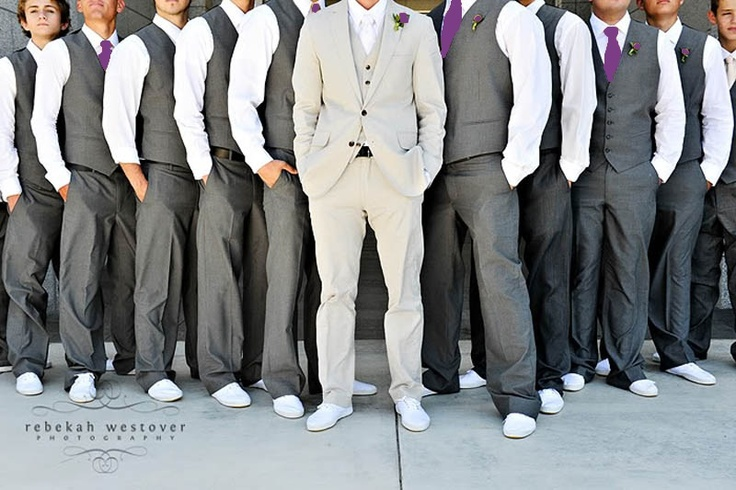 Purple and grey groomsmen with just vests. Groom with a jacket in an accent color.