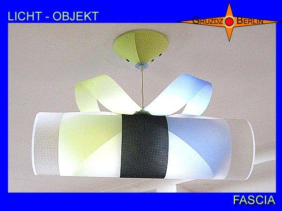 Hier unsere Leuchte FASCIA aus einem anderen Blickwinkel,Lampe mit Baldachin transluzent. Zwei farbige Bänder durchfließen bei der Pendelleuchte FASCIA den transluzenten Zylinder und geben ihm Farbe und Harmonie. Ergänzend wirken die schwarzen und weißen Streifen aus Gitternetzgewebe Batyline als Abschluss und Mitte. Faszination in Farbe und Form.