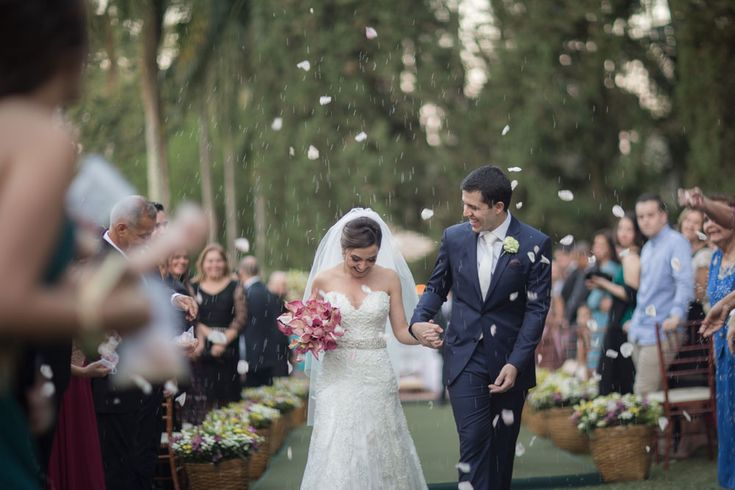 7 indicações incríveis de fotógrafos para casamento que a gente ama. Fotografia: Ricardo Hara. Casamentos ao ar livre rústico. Chuva de arroz e pétalas de flores para noivos que saem da cerimônia de casamento no campo.