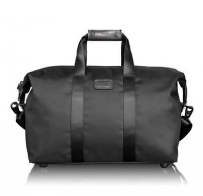 TUMI  SMALL SOFT TRAVEL SATCHEL  €346  A handy travel bag is made from Tumis characteristic ballistic nylon. It is perfect for simple overnight stays or short vacations. Despite its slim size, the bag has a roomy main compartment with a zippered pocket and key holder. The bag has convenient carrying handles in leather and a removable, adjustable shoulder strap.