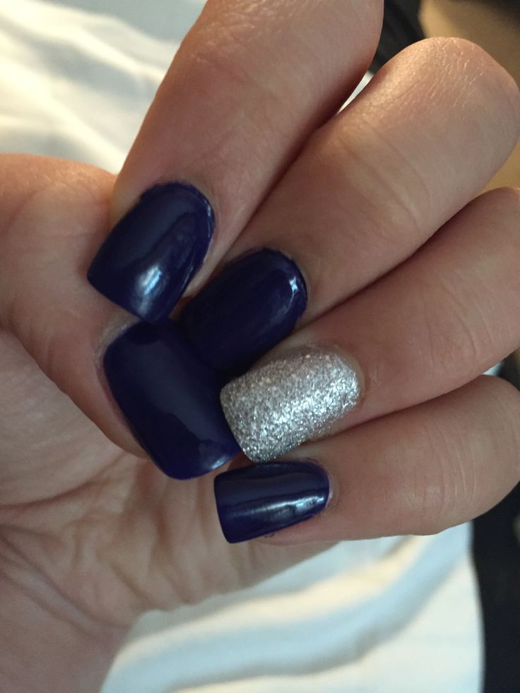 Acrylic nails done with dark navy blue and silver sparkles accented on the ring finger