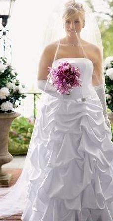 novias curvilineas.Vestido de novia de satén con corsé, con detalle de lazo y broche en la cintura, y falda recogida bombacha hasta el piso.