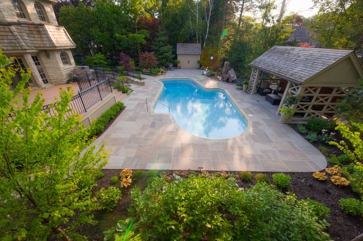 Another view of this project highlights the new rectangular flagstone pool deck, a covered pavilion sitting area, gorgeous generous garden beds, a composite wood deck, and a handsome storage shed.
