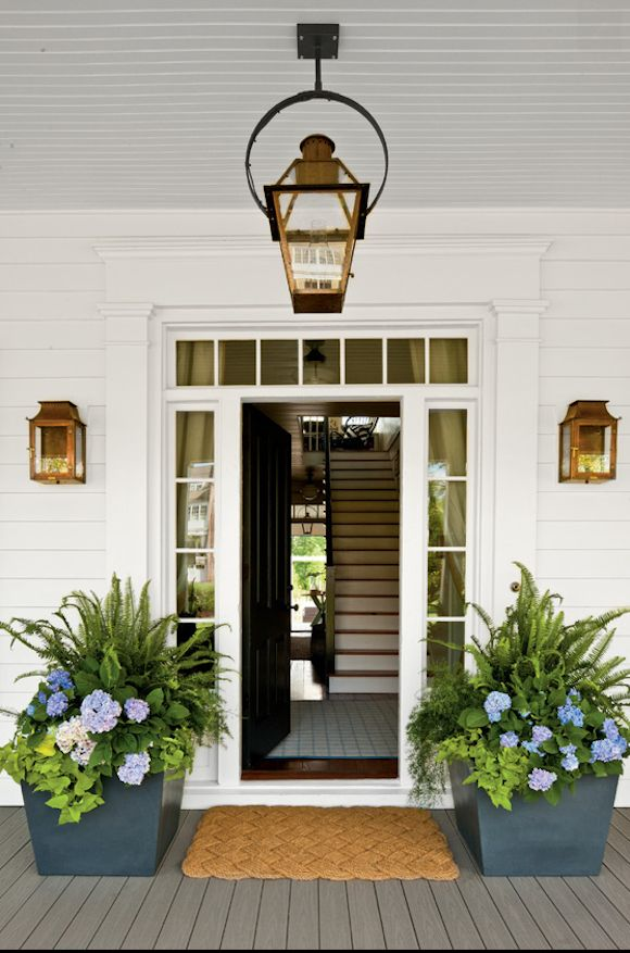 Planters. So inviting, clean and crisp white front porch with lanterns, and painted gray porch floor.